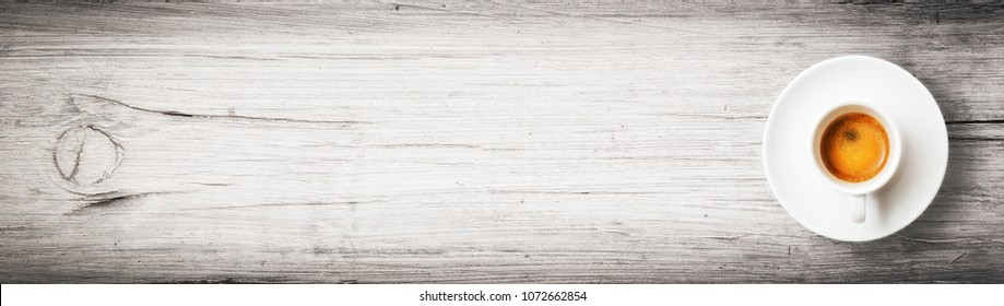 A cup of espresso coffee on a white wooden background