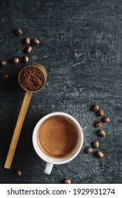 Cup espresso and measuring spoon with ground coffee, top view