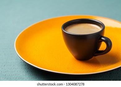 Cup of espresso on bright orange background