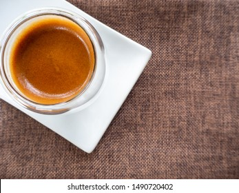 Cup of espresso on the table. glass beaker for shot-cocktail or coffee drinks. Close up of a glass of espresso. Hot coffee in a glass with double walls isolated on a white background.