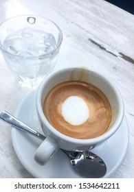 A cup of espresso on a table. White cup of double espresso on wooden table together with a glass of ice water. Healthy drink during meal break cup of coffee.