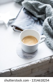 Cup of espresso on white table with cozy interior details