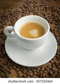 Cup of espresso on wooden table with coffee beans
