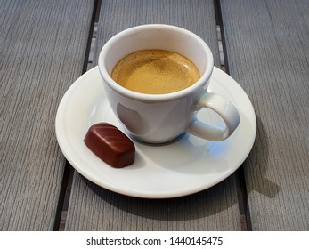 Cup of espresso with small chocolate praline on rustic gray table.