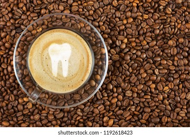 Cup of espresso with tooth sign on coffee foam on coffee beans background. With copy space.