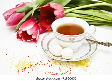 cup expecting with candies and pink tulips