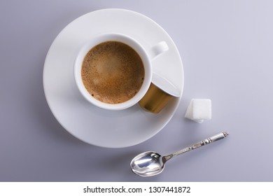 Cup of expresso coffee seen from above with sugar lumps, a silver spoon and a coffee capsule.
