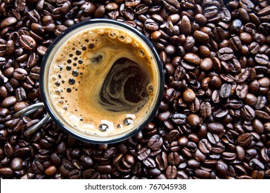 Cup of expresso and roasted coffee beans in the background. Coffee Bean