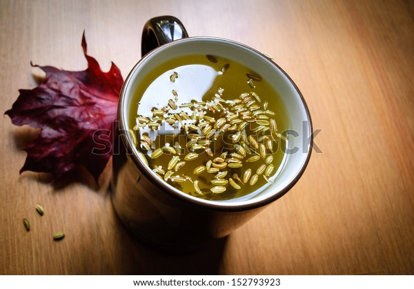 Cup of fennel tea with seeds on wooden background with maroon maple leaf decoration.