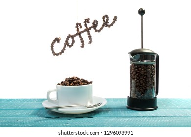 A cup filled with coffee beans on a weathered table with the word coffee above with a white background