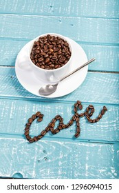 A cup filled with coffee beans on a weathered table with the word cafe