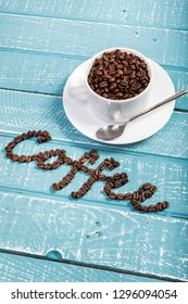 A cup filled with coffee beans on a weathered table with the word coffee