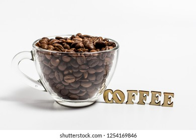 Cup filled with grains of coffee and the inscription coffee