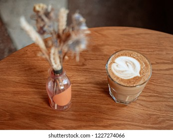 Cup of flat white coffee and dry flowers in small bottle on tabletop in cafe.