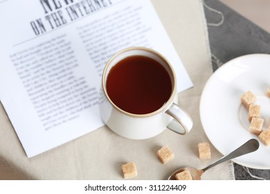 Cup of flavored coffee with lump sugar on table with napkin and newspaper, closeup