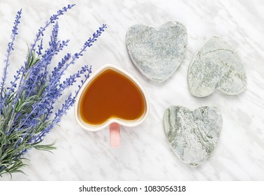 Cup of flavored tea and blue lavender. Love for tea. Flat lay composition with heart-shaped mug and stone hearts.