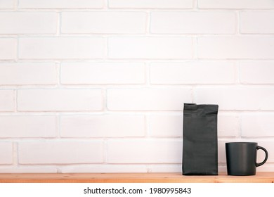 Cup and foil pack of coffee on a wooden table against a background of a clean white brick wall. Coffee concept with copy space