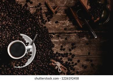 Coffeebeans cup of fragrant black coffee and coffee grinder on wooden table seen from above