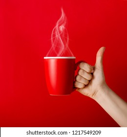 Cup of fragrant coffee in hand on a cool day. Black warm coffee in cold weather.Coffee on a red background for your design. Advertising coffee.