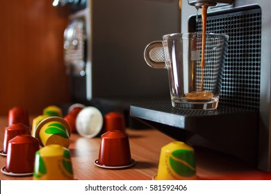 A cup of fragrant coffee on the coffee machine. Coffee pouring into the cup. Wooden table background.