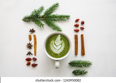 A cup of fragrant and tasty green matcha latte coffee on a white surface decorated in a Christmas style.