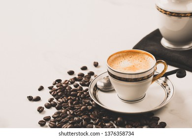 Cup of fresh americano or espresso coffee with roasted coffee beans on white marble table background. Morning hot drink, coffee break, copy space