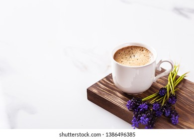 Cup of fresh americano or espresso coffee with golden foam froth on pile of brown raw coffee beans on white marble table background. Morning hot drink, coffee break, cope space