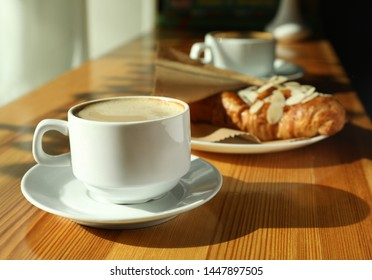 Cup of fresh aromatic coffee and croissant at table in cafe