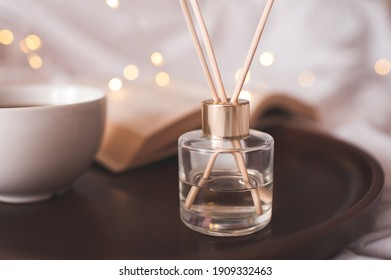 Cup of fresh black coffee with open paper book and liquid home perfume in glass bottle with sticks over glowing lights in bed close up. Cozy atmosphere. Good morning.