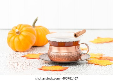 Cup of fresh brewed chai tea with fall leaves.
