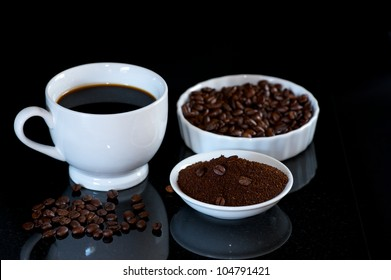Cup of fresh brewed Coffee with plates of coffee beans and ground coffee.