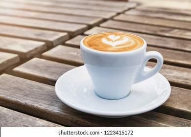 Cup of fresh cappuchino with heart drawn on the foam on the street wooden table close-up