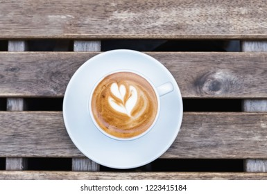 Cup of fresh cappuchino with heart drawn on the foam on the street wooden table top view