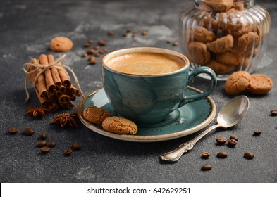 Cup of fresh coffee with Amaretti cookies on dark background, selective focus