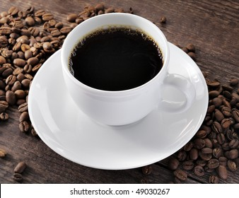 A cup of fresh coffee and coffee beans