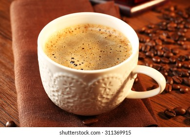 Cup of fresh coffee with beans on table, closeup