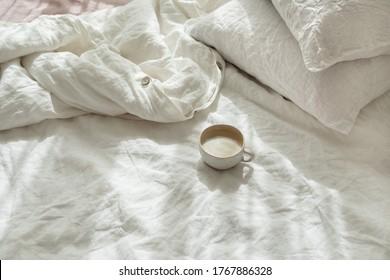 Tasse frischer Kaffee im Bett, Morgenstimmung. Bettwäsche aus Baumwolle, Stoffwäsche. Bio- und Naturwäsche. Gemütliches Zimmer-Interieur. Schönes Licht.