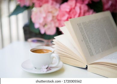 Cup of fresh coffee, book and flowers on a table. Cosy, time for yourself concept.