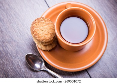 cup of fresh coffee with a cookie and spoon in a studio