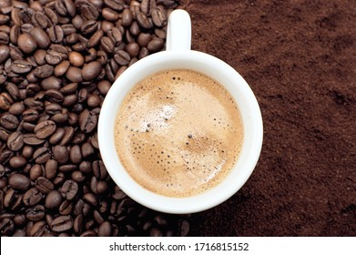 A cup of fresh coffee with foam. Background of coffee beans and ground coffee.