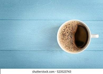 Cup of fresh coffee on blue wooden background, top view
