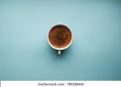 A cup of fresh coffee on blue background with text space.
