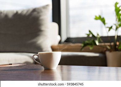 cup of fresh coffee standing on the table against window