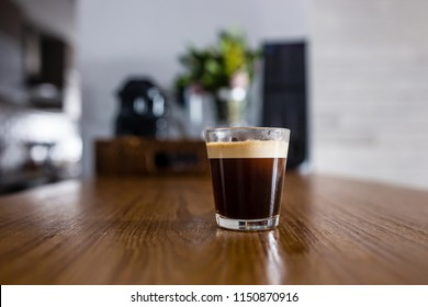 cup of fresh espresso coffee on wooden kitchen counter with interesting perspective, with cup in focus and blurred background