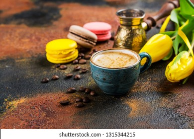 Cup of fresh ground coffee, jezve, yellow tulips and french macaroons on grunge background, Copy space