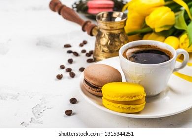 Cup of fresh ground coffee, jezve, yellow tulips and french macaroons on white background, Copy space