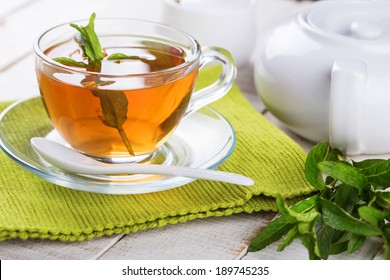 Cup of fresh herbal tea on wooden table. Selective focus, horizontal.