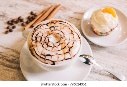 cup of fresh hot cappuccino with cinnamon sticks, on wooden table