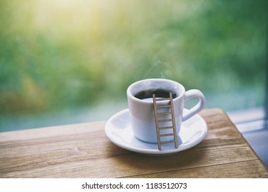 cup of fresh morning coffee with toy ladder as symbol of sinking in aroma and taste