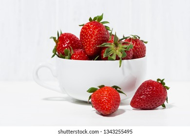 cup of fresh strawberries on a white background, closeup horizontal